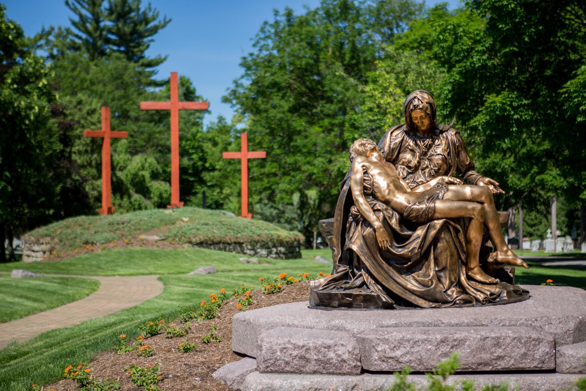 Pieta monument in front of 3 crosses