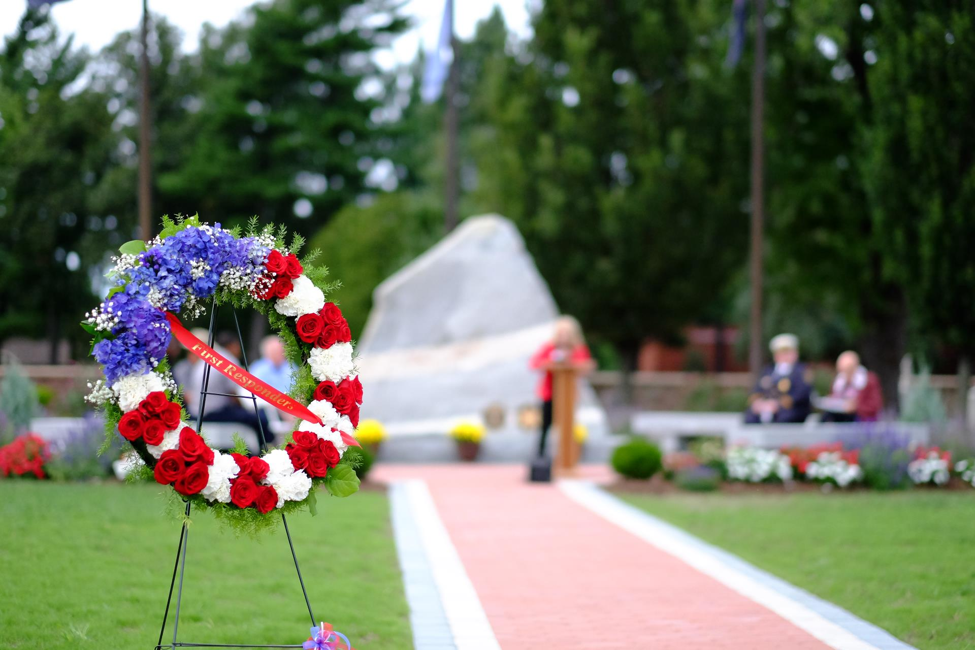 Photo of a Red, white, and blue wreath at a military ceremony